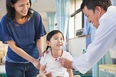 Kinderarzt, der kleines Mädchen, ihre Mutter neben ihr überprüft Stockfotos