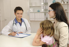 Kinderarzt, der mit Mutter und Kind spricht Lizenzfreie Stockbilder