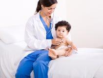 Kinderarzt, der Schätzchen überprüft Lizenzfreies Stockfoto
