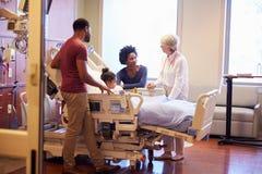 Kinderarzt-Visiting Parents And-Kind im Krankenhaus-Bett Stockfotos