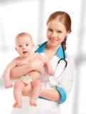 Kinderarztfrauendoktor, der geduldiges Baby hält Lizenzfreies Stockfoto