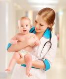 Kinderarztfrauendoktor, der Schätzchen anhält Stockfoto
