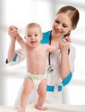 Kinderarztfrauendoktor, der Schätzchen anhält Stockfotos