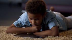 Kinderaufpassendes Video auf der Tablette, zu Hause gebohrt, schlecht organisierte Freizeit für Kind lizenzfreies stockbild