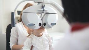 Kinderaugenheilkunde - Optometriker Checks Eye des kleinen Mädchens stockbild