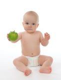 Kinderbabykleinkind, das in der Windel sitzt und grünen Apfel isst Stockbild
