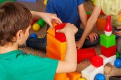 Kinderbausteine im Kindergarten Gruppenkinder, die Spielzeugboden spielen lizenzfreie stockbilder