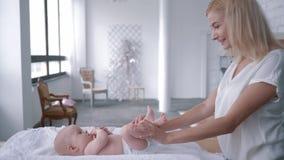 Kinderbetreuung, junge Mutteränderungswindel zu ihrem neugeborenen Mädchen auf ändernder Tabelle zu Hause nimmt dann das Baby in  stock footage