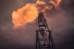 Kinderbewundern szenischer Sonnenuntergang mit schönen Wolken und Hände zum Himmel heraus erreichen Lizenzfreies Stockbild