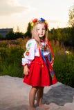 Kinderbildmädchen im ethnischen ukrainischen Kostüm auf einer Wiese im Sommer stockfotos