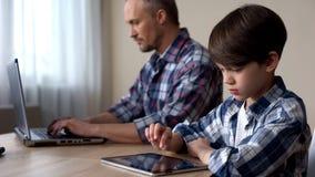Kinderblättern auf Tablette, Vater, der an Laptop-Computer, Mangel an Aufmerksamkeit arbeitet stockfotos