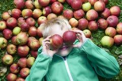 Kinderblonder Junge, der auf dem Hintergrund des grünen Grases mit Apfelgläsern liegt Lizenzfreies Stockfoto
