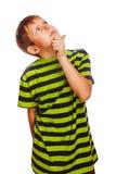 Kinderblonder Junge im grünen T-Shirt denkt das Verkratzen Lizenzfreies Stockfoto