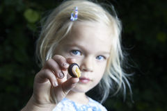 Kinderblondes Mädchen, das kleine junge Schnecke zeigt und studiert Stockbilder