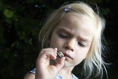 Kinderblondes Mädchen, das kleine junge Schnecke zeigt und studiert Stockfoto