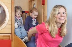 Kinderdagverblijf nures met twee jonge geitjes op dia Stock Foto