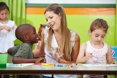 Kinderdagverblijfleraar die aan jongen spreken Stock Foto