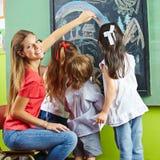 Kinderdagverblijfleraar en kinderen Stock Afbeelding