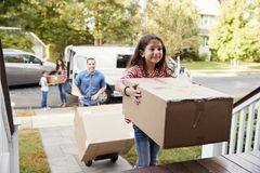 Kinderdas helfen entladen Kästen von Van On Family Moving In-Tag lizenzfreie stockfotos