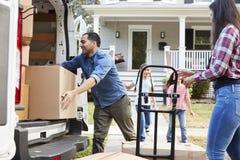 Kinderdas helfen entladen Kästen von Van On Family Moving In-Tag lizenzfreies stockbild