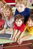 Kinderen in basisschool met laptop stock foto