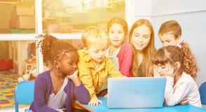 Kinderen bij de computer met opvoeder in kleuterschool stock foto