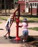Kinderen bij de Pomp van het Water Stock Foto