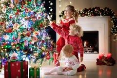 Kinderen bij Kerstboom Jonge geitjes bij open haard op Kerstmisvooravond Royalty-vrije Stock Fotografie