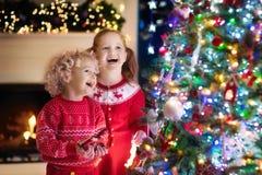 Kinderen bij Kerstboom Jonge geitjes bij open haard op Kerstmisvooravond Royalty-vrije Stock Foto