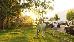 Kinderen in de afstand in het stadspark in werking worden gesteld na school die schoolvriendschap, terug naar school stock video