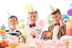 Kinderen dichtbij lijst met traktaties bij verjaardagspartij binnen royalty-vrije stock afbeeldingen