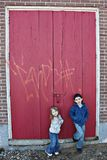 Kinderen dichtbij rode houten deur royalty-vrije stock afbeelding