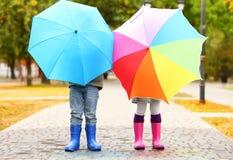 Kinderen die achter heldere paraplu's verbergen Stock Afbeeldingen