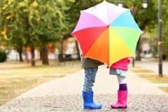 Kinderen die achter kleurrijke paraplu verbergen Royalty-vrije Stock Foto's