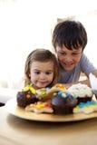 Kinderen die banketbakkerij thuis eten stock afbeeldingen