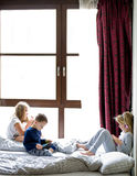 Kinderen die in bed met hun tabletten en telefoons spelen royalty-vrije stock fotografie