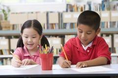 Kinderen die bij bureau zitten en in klaslokaal schrijven Stock Foto's
