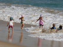 Kinderen die bij het strand, gelukkige dagen spelen stock afbeeldingen