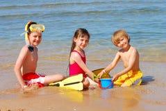 Kinderen die bij het strand spelen Stock Afbeeldingen