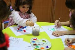 Kinderen die bij kleuterschool schilderen Stock Afbeelding