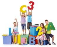 Kinderen die bij kubus zitten. stock afbeeldingen