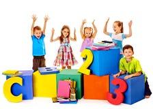 Kinderen die bij kubus zitten. stock foto