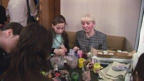 Kinderen die bij lijst verschillende kleurrijke cijfers schilderen handmade verwezenlijking Tekeningslijst hobby stock footage