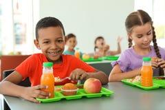 Kinderen die bij lijst zitten en gezond voedsel eten stock foto