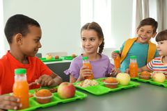 Kinderen die bij lijst zitten en gezond voedsel eten stock afbeelding