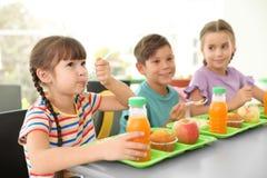 Kinderen die bij lijst zitten en gezond voedsel eten royalty-vrije stock foto