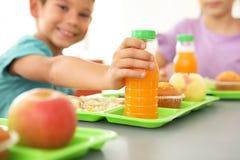 Kinderen die bij lijst zitten en gezond voedsel eten royalty-vrije stock foto's