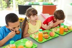 Kinderen die bij lijst zitten en gezond voedsel eten tijdens onderbreking royalty-vrije stock afbeeldingen