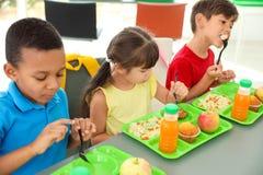 Kinderen die bij lijst zitten en gezond voedsel eten tijdens onderbreking stock foto's