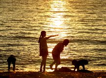 Kinderen die bij zonsondergang op strand spelen stock fotografie